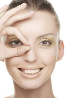 Woman holding her fingers over her right eye